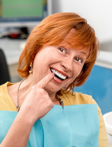 Senior woman pointing to implant supported denture