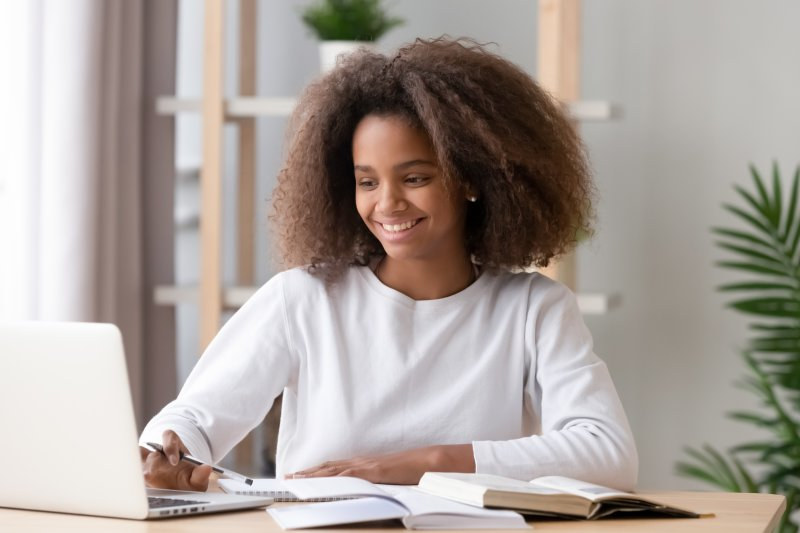 Teen girl smiling while doing homework