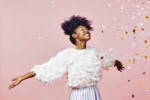 young woman celebrating the new year against a pink background